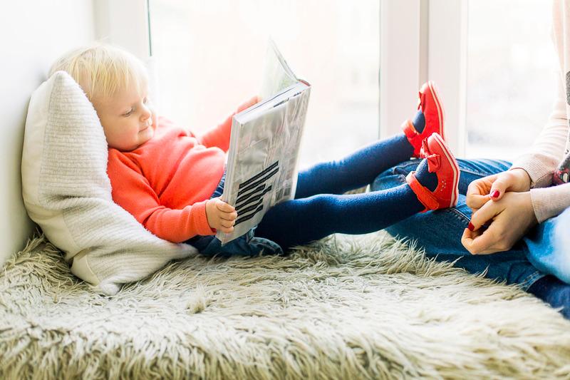 Laps loeb voodis raamatut